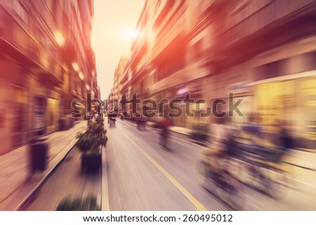 Abstract background - people shopping, walking and riding bikes in main shopping street in Palermo, Italy - radial zoom  blur effect defocusing filter applied, with vintage instagram look. - stock photo