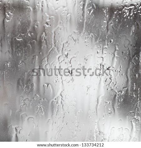 abstract background rain streams on home glass window - stock photo