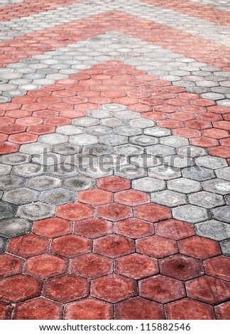 Abstract background texture of cobblestone paving road with red and gray arrows - stock photo
