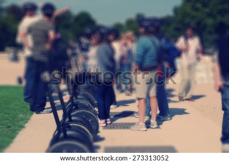 Abstract background. Tourists near the segways in the park. Paris, France. Blur effect defocusing filter applied, with vintage instagram look. - stock photo