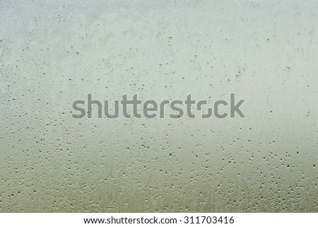 Abstract background water droplet on a restroom window with shading sunlight (Blurred wallpaper) - stock photo