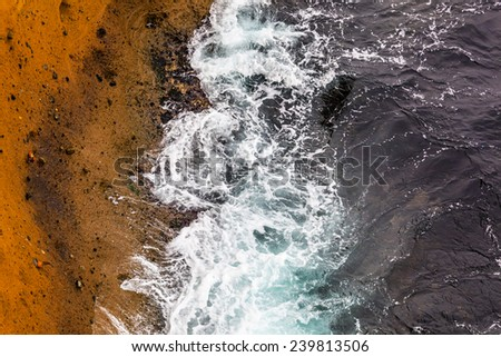 Abstract background - wavy sea meets rocks. - stock photo