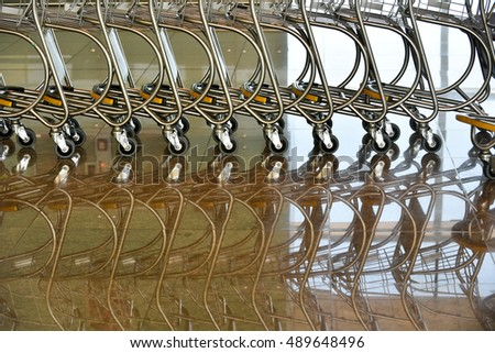 Abstract baggage trolleys at airport. Floor reflection.