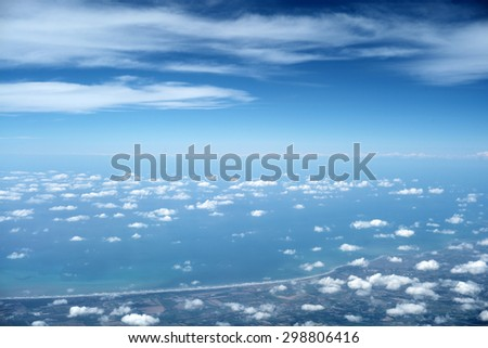 Abstract beautiful outer view from flight of air hight space with clear blue sky and white fluffy air clouds and ground with sea coast sunny day on natural background, horizontal picture - stock photo