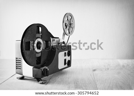 abstract black and white image of old 8mm Film Projector over wooden table and textured background - stock photo