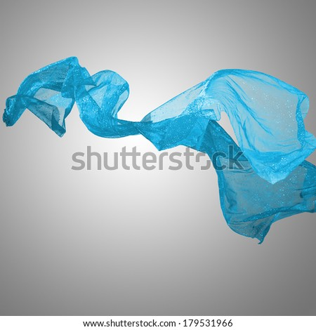 Abstract blue flying motion fabric over gray background - stock photo