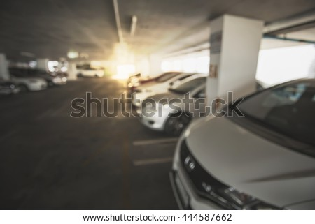Abstract blur background of car in parking indoor with lighting warm tone.