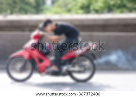 Abstract blur Dangerous speedy motorbike, No helmet, White smoke, speeds up to cross the bridge. - stock photo