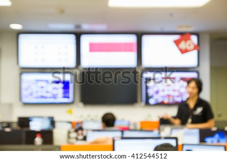 abstract blur focus A man is standing before LED Tv monitor and talk with his team about problem issue in Network Operation Center room   - stock photo