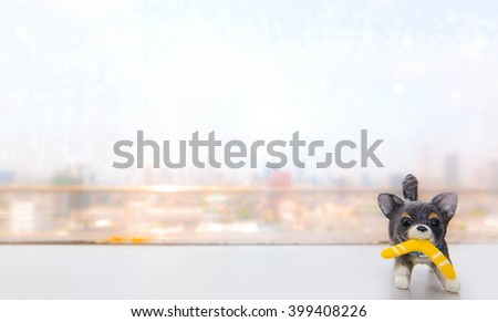 Abstract Blur of a cityscape with miniature of a dog on the foreground, copy scape or for background. Selective focus on the dog's eyes (Pet in a city concept) - stock photo