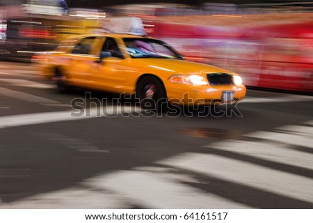 Abstract blur of a night time urban street scene with a yellow taxi cab speeding by.  Slow shutter speed panning technique used for motion blur. - stock photo