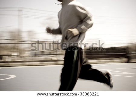 Abstract blur of a young man warming up by jogging at the basketball court.  Intentional motion blur. - stock photo