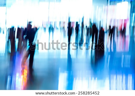 abstract blur of passengers rushing at big city station. - stock photo