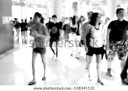 Abstract blur people walking in fashion mall. Black and white filter.