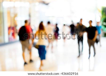 Abstract blur people walking in fashion mall. The light come straight from front door. - stock photo