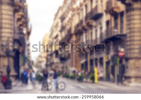 Abstract blurred background of pedestrians walking and talking and bikers on bikes - rush hour and busy traffic in Italian city Palermo. Blur effect defocusing filter, with vintage instagram look. - stock photo