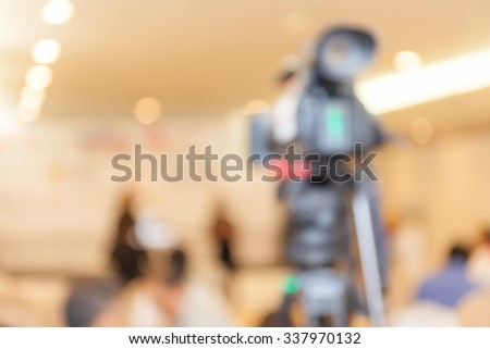 Abstract blurred background of video camera recording in press conference. - stock photo