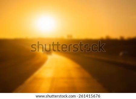 Abstract blurred background with a rural highway with sun setting close to horizon, reflecting off the roadway - stock photo