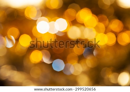 abstract blurred background - yellow and brown shimmering Christmas lights bokeh of electric garlands on Xmas tree - stock photo