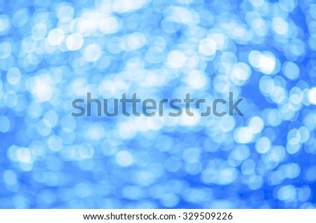 Abstract blurred blue background with sun reflection on the water. True bokeh. - stock photo