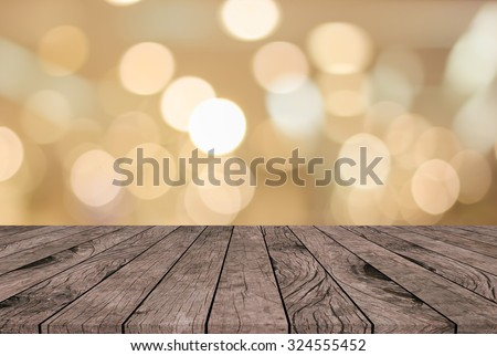 abstract blurred bokeh shine in warn tone backdrop with vintage grungy beige brown wood backgrounds textures with tabletop:show your products on this display.merry christmas and new year backdrops - stock photo