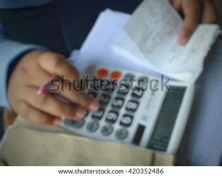 Abstract blurred close up of man with calculator counting money and making notes at office  - stock photo