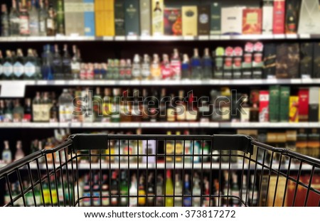 Abstract blurred image of alcohol store with trolley in department store. (Selective focused at shopping cart) - stock photo