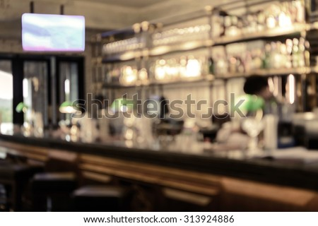 Abstract blurred image of bar counter with bottles of whiskey and wine, Vintage tone - stock photo