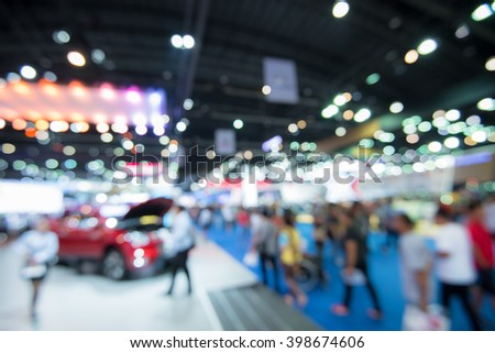 Abstract blurred image of people in cars exhibition show  - stock photo