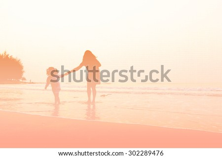 Abstract blurred Mother and children playing on the sunset beach on fabric textured background, pastel style.