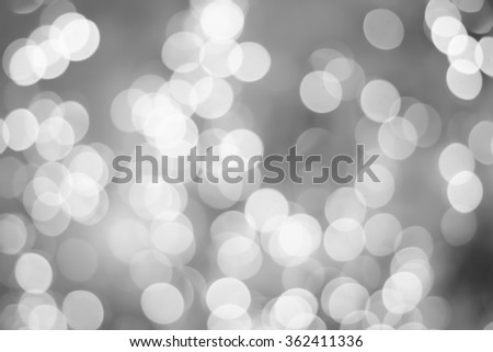 abstract blurred of sparkle bokeh light in black and white background:blurry circle shiny bulbs in gray scale tone colored.image display for design,decorate:christmas and new year backdrop picture.  - stock photo