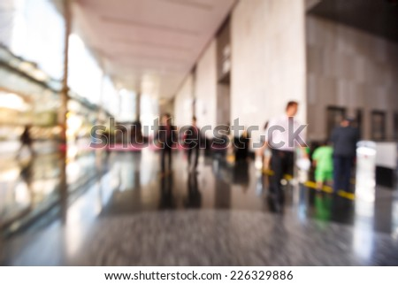 Abstract blurred people walking or standing in office building - stock photo