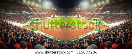 Abstract blurred photo crowd of spectators on a stadium with a football match, sport background concept - stock photo