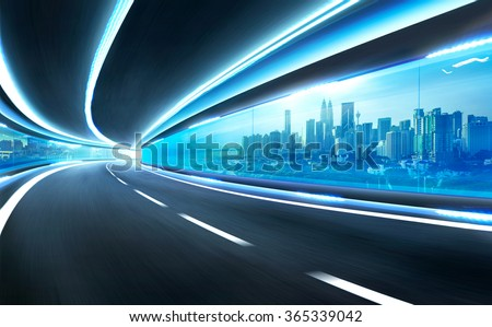 Abstract blurred speed motion road in glass tunnel over the city - stock photo