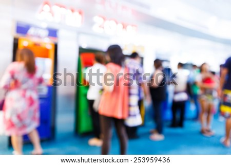 Abstract Blurry people with automatic teller machine or ATM in shopping centre - stock photo