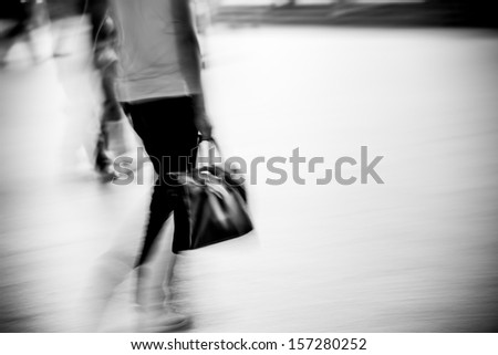 abstract business woman with bag walking on city street, black and white motion blurred. - stock photo