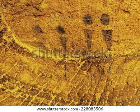 Abstract children art in sandstone cave. Black carbon paint of human hunting on sandstone wall, copy of prehistoric picture.  - stock photo