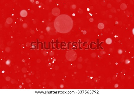 Abstract circles blur christmas holiday design element. Falling snow bokeh effect on red background. - stock photo