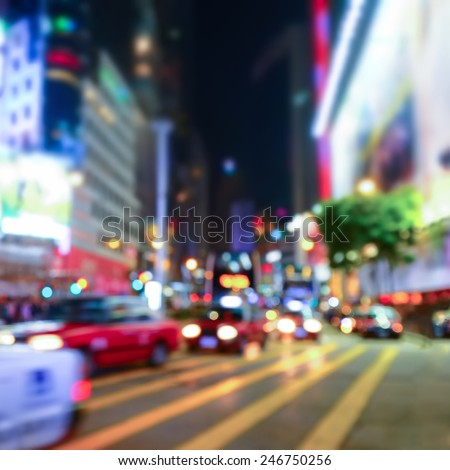 Abstract cityscape blurred background. Night view of modern city crowded street with illuminated skyscrapers, cars and walking people. Hong Kong - stock photo