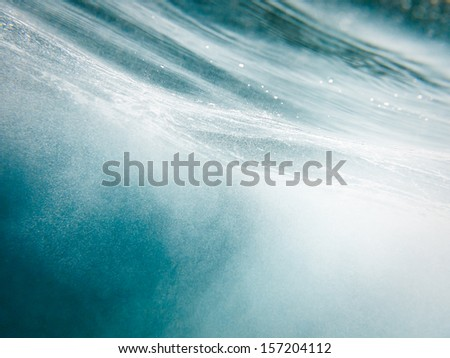 Abstract clear turquoise blue horizontal streaked water pattern with air bubbles from underwater - stock photo