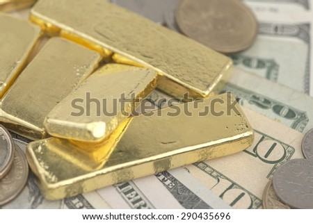 Abstract closeup pile of gold bars over dollar coins and banknotes - stock photo