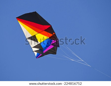 Abstract, colorfull kite in a blue sky - stock photo