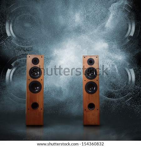 Abstract concept of powerful audio speakers blast out a cloud of dust against dark background - stock photo
