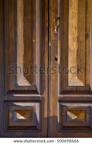 abstract cross   brass brown knocker in a   closed wood door   varese italy sumirago sunny day