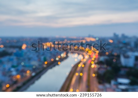 Abstract curve festive background with bokeh defocused lights of downtown of  Ho Chi Minh City ( Sai Gon ) , Vietnam from high view at  in sunset or sunrise - stock photo