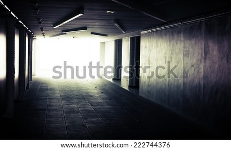 Abstract dark underground corridor interior with glowing end - stock photo