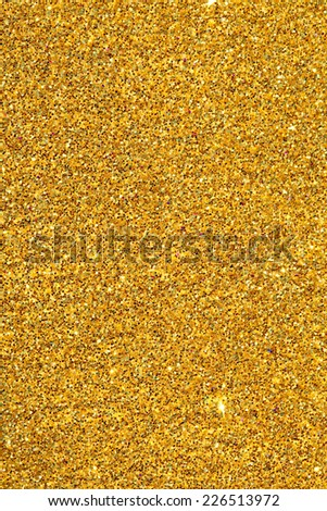 Abstract detail background of a vivid bright gold glitter shining and sparkling with texture. Galaxies and stars, full frame yellow noise color backdrop element. Vertical view. - stock photo