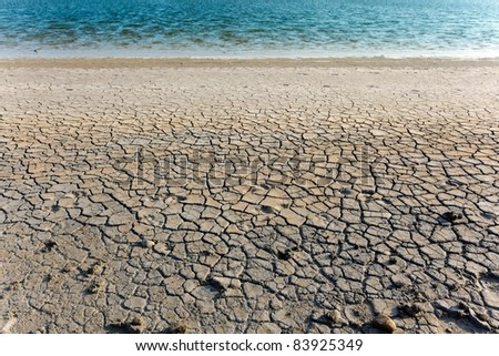 abstract dry soil  and blue water - stock photo