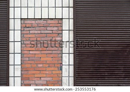 abstract facade of the building with a facing tile and a bricklaying and iron blinds - stock photo