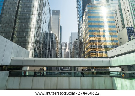 Abstract futuristic cityscape view with modern skyscrapers and people walking on bridge. Hong Kong - stock photo